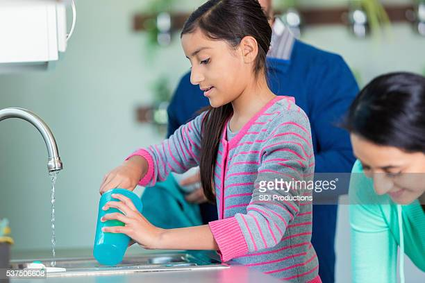 Pre-teen girl helps parents clean up after dinner