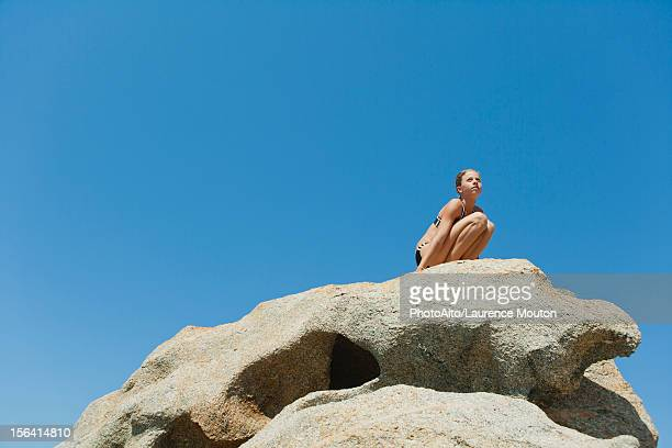Preteen girl in bikini crouching on rock against blue sky, low angle view