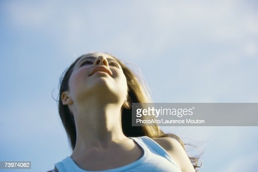 Preteen girl, low angle view, sky in background : Stock Photo