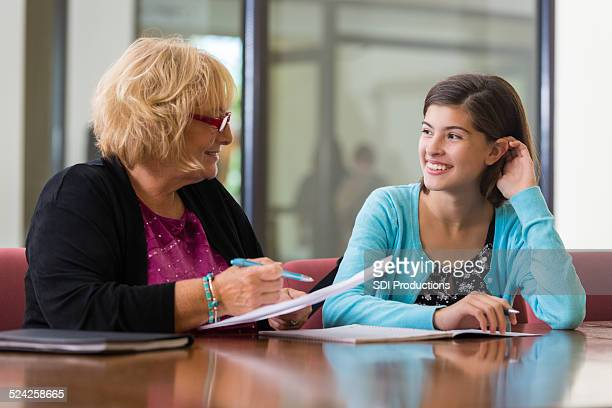 Preteen girl meeting with school counselor or therapist