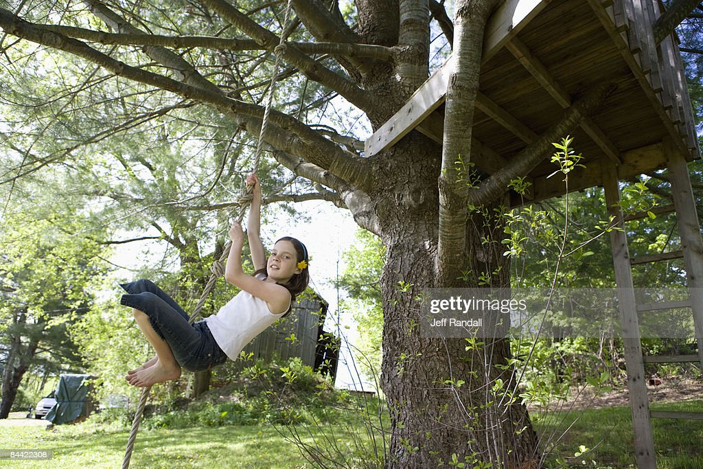 Pre-teen girl on rope swing in back yard : Stock Photo