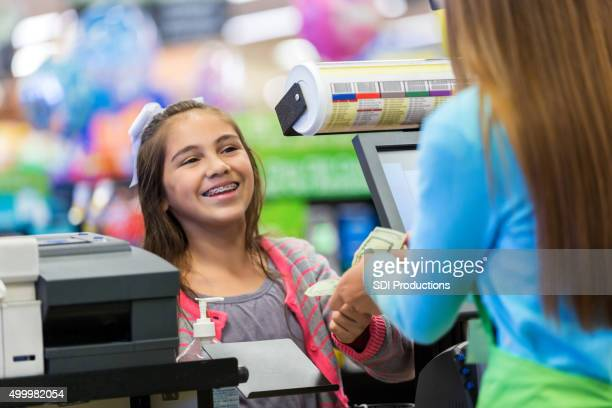 Preteen girl paying for purchase at grocery store