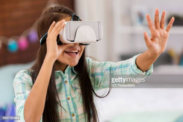 Preteen girl plays with virtual reality headset