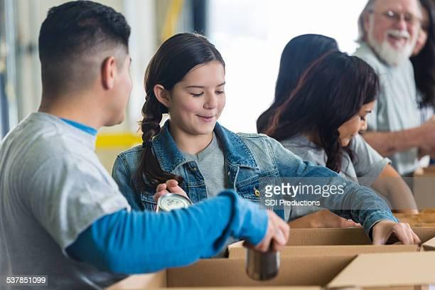 Preteen girl sorting donations in food bank with volunteers