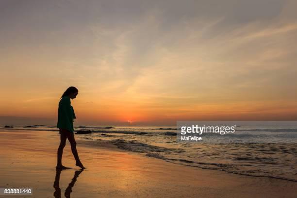 Preteen fille debout sur la plage au coucher du soleil à Fernando de Noronha