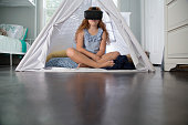Preteen girl using virtual reality goggles in tent