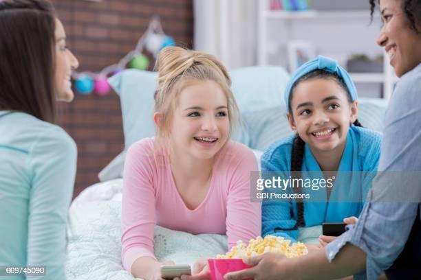 Preteen girls enjoy popcorn during sleepover