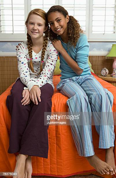 Preteen girls seated on bed