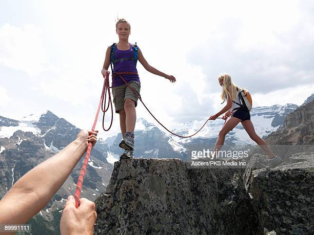 Pre-teen girls traverse mountain ridge, with rope