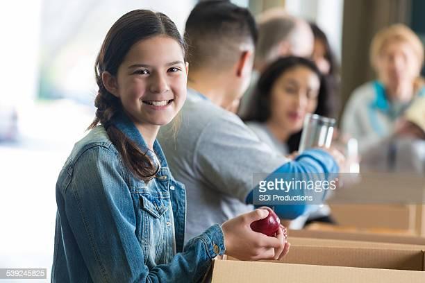 Preteen Hispanic girl sorting donations with food bank bank volunteers