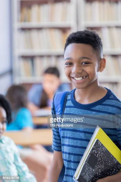 Preteen male student smiles for camera at school