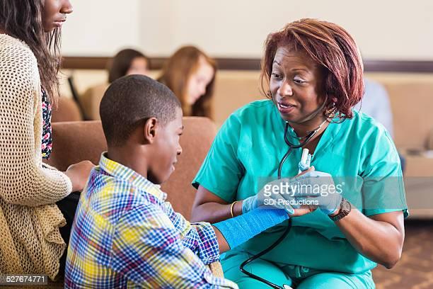 Preteen patient examiné par infirmière à l'hôpital de la zone d'attente