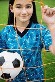 Preteen soccer player behind net
