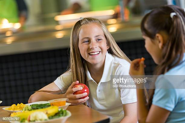 Preteen student eating healthy lunch in school cafeteria with classmate