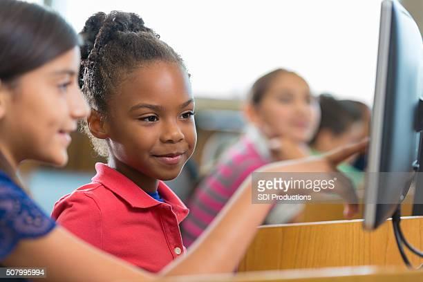 Bonita americana africano escola primária estudante usando um computador na biblioteca