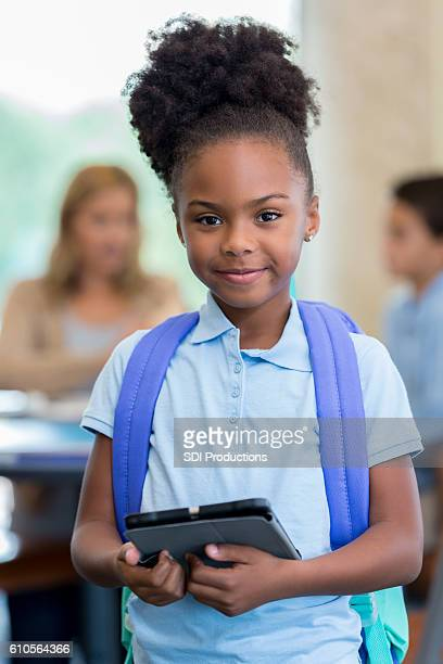 Pretty African American elementary schoolgirl with tablet before school