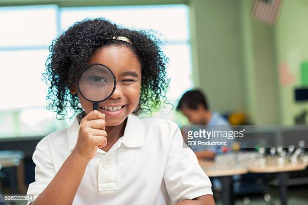 Pretty African American girl looks through magnifying glass