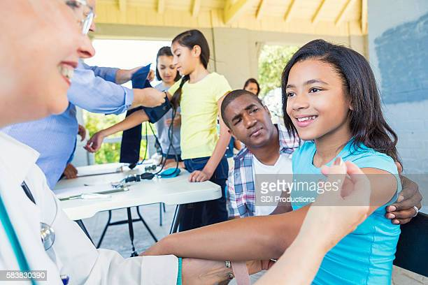 Pretty African American girl smiling at her doctor