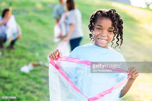 Pretty African American Girl volunteering at park clean-up