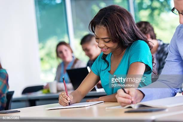 Abbastanza afro-americana giovane donna assumendo test in classe college