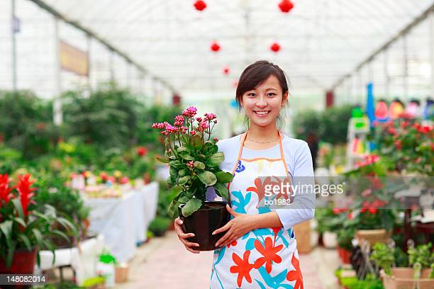 pretty asian Florist holding flower in the shop