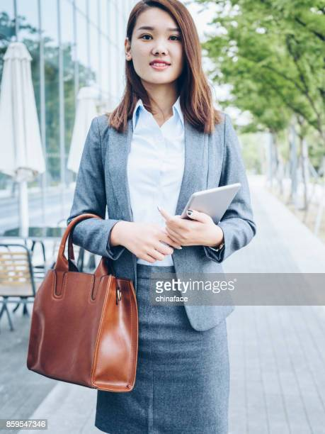 pretty asian girl walking outside office building with holding tablet PC