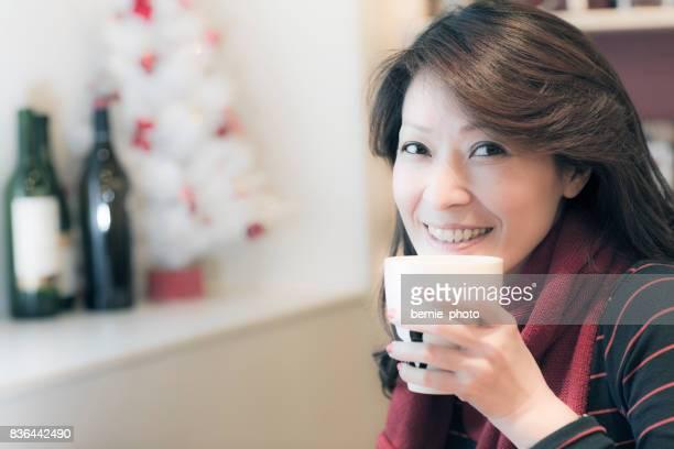 Mujer bonita asiática tomando café en el interior