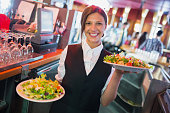 Pretty barmaid holding plates of salads in a bar
