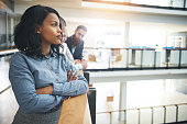 Attractive young African-American businesswoman standing in office with arms crossed and looking away thoughtfully.