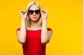 pretty blond lifeguard in red swimsuit and sunglasses on yellow background
