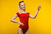 pretty blond lifeguard in red swimsuit and sunglasses points finger up on yellow background