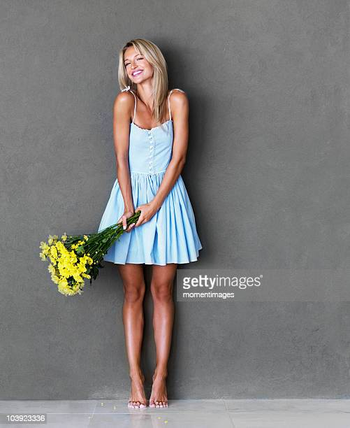 Pretty blond woman holding a bouquet of flowers