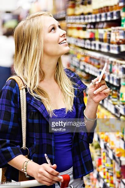 Pretty blonde checks supermarket shelf against her shopping list
