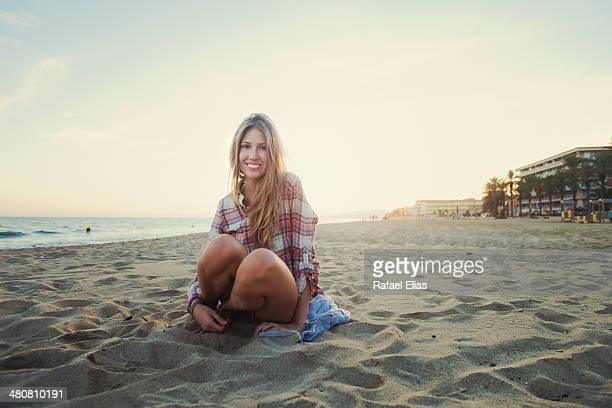 Pretty blonde girl sitting on the beach