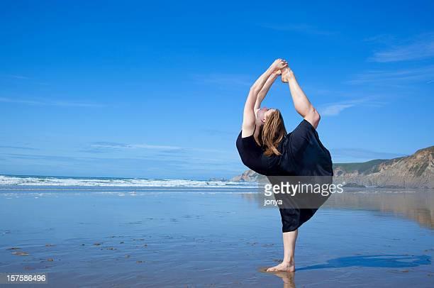 pretty blonde gymnast striking a pose on the beach