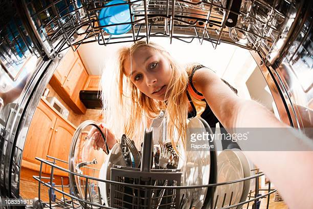 Pretty blonde loads dishwasher: seen from inside the machine