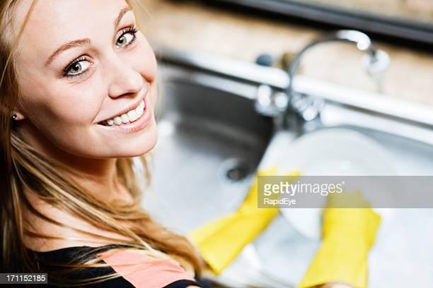 Bonita rubia sonrisas cheerfully como ella lavar los platos