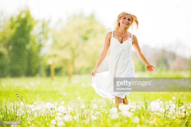 Pretty blonde wearing white dress is walking in the park
