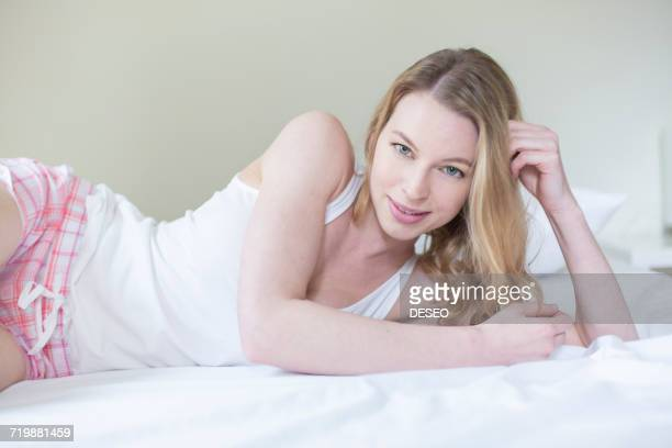 Pretty blonde woman lying in bed smiling at camera