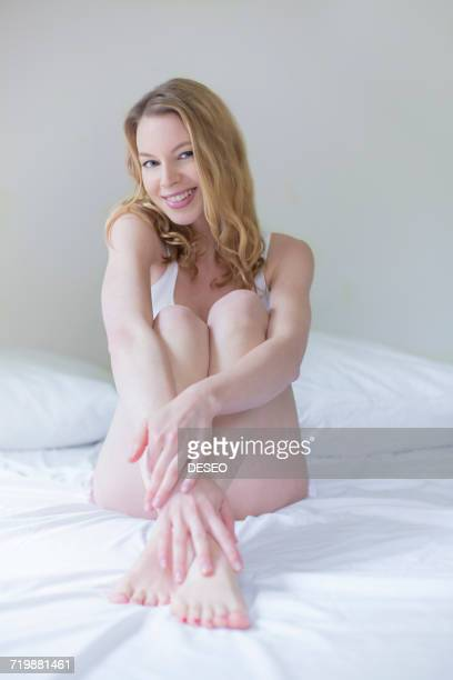Pretty blonde woman sitting in bed smiling at camera