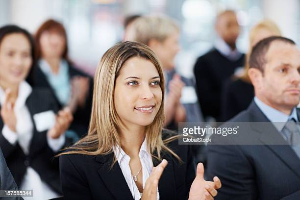 Pretty business woman applauding with colleagues during a seminar