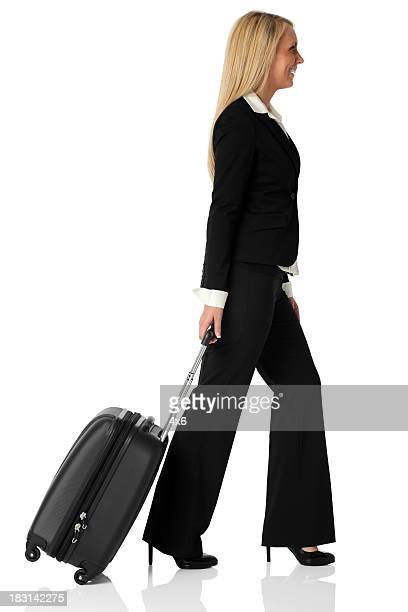 Pretty businesswoman pulling her suitcase