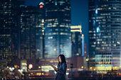 Pretty businesswoman using digital tablet in city