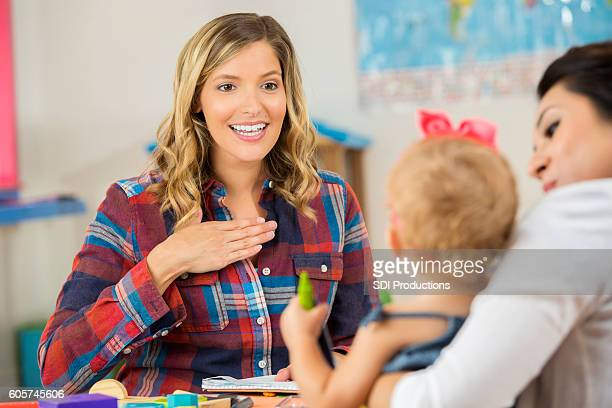Pretty Caucasian teacher showing a preschooler sign language