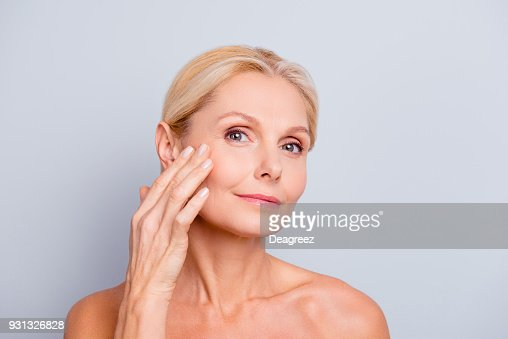 Pretty, charming, attractive woman touching, enjoying her perfect face skin, holding fingers on cheek, pimple, whelk, pustule, dry, oiled, problem skin concept, isolated on grey background : Foto stock