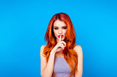 Pretty charming young  woman having secret while holding finger on lips and showing silence sign while standing on blue background