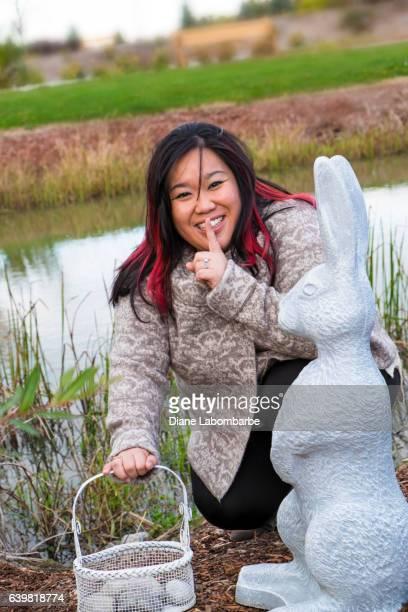 Pretty Chinese Woman Peeking Around a Cement Garden Ornament
