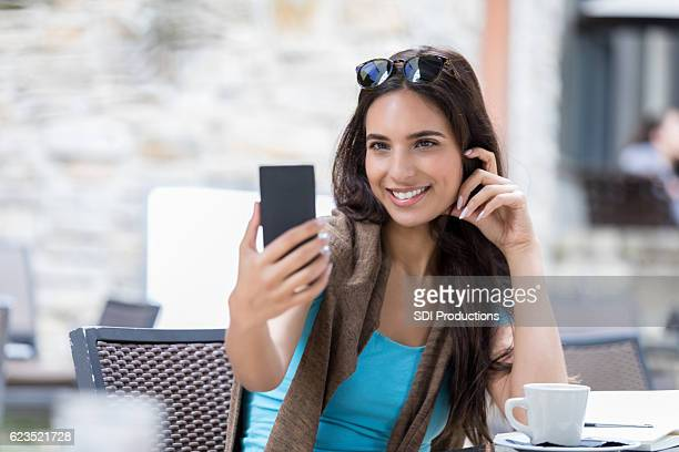 Pretty college student takes selfie at coffee shop