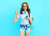 Pretty cool woman listens music and using smartphone over colorful blue background