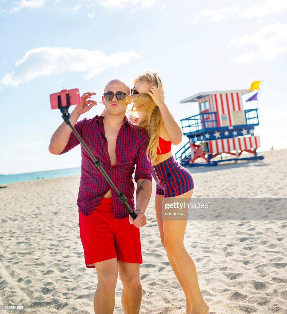 Joli Couple à l'aide d'une autophoto stick, à Miami Beach : Photo